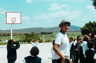 Saul Flores standing with elementary school students in Atencingo, Mexico.
