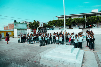 Elementary school students standing in front of their school in Atencingo, Mexico.
